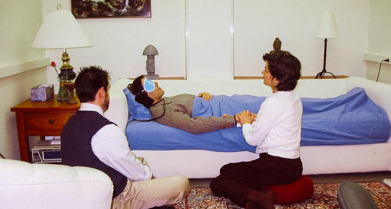 En kvinnelig og mannlig terapeut holder hånden til en mann under psykedelisk terapi