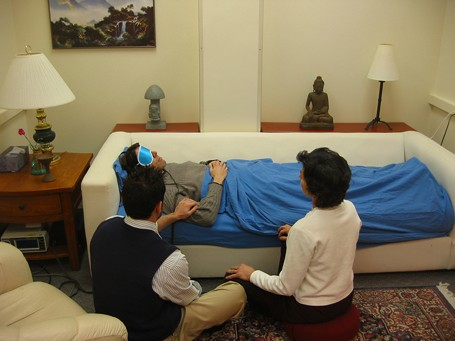 A person treated with psychedelics (psilocybin) on a couch with blindfolds and headphones with two therapists / psychologists
