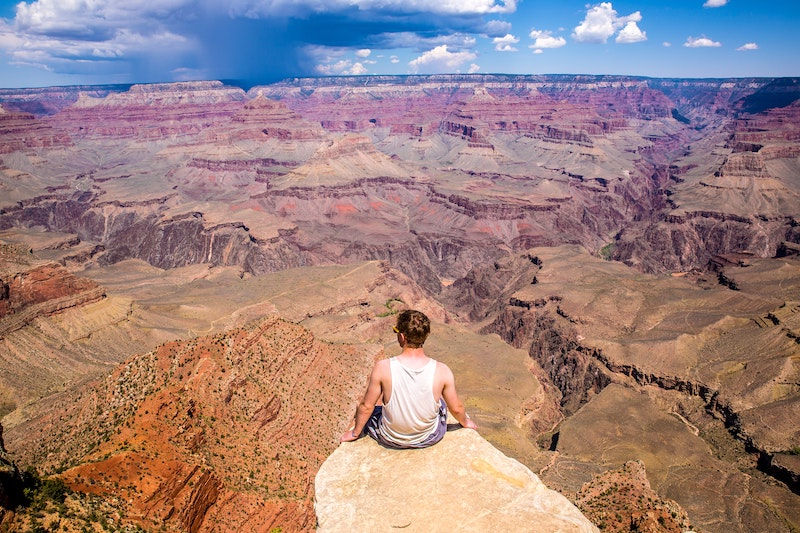 man sitting on the edge of a mountain